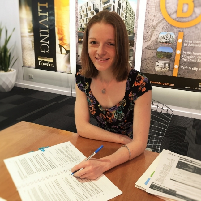 Brittany signing her contract at the Bowden Sales Centre in December 2015